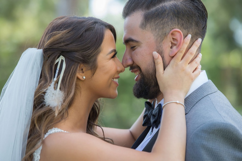 bride holding groom face and touching nose eskimo kisses bride with veil and feather hair accessory