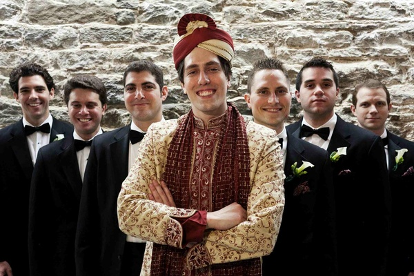 Groom in Hindu wedding attire and groomsmen in tuxedos