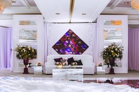 White lounge furniture around dance floor flower arrangements diamond purple art and accessories