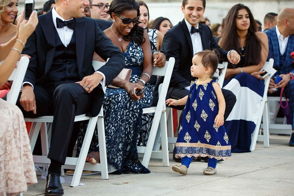 a little toddler in a pakistani dress of blue and gold walks down aisle during ceremony