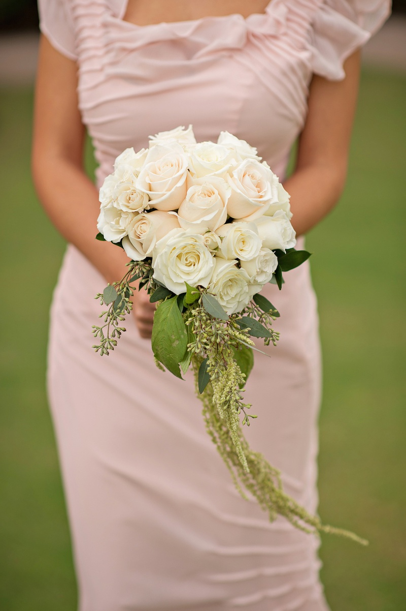 Bridesmaid in pink dress holding white rose and light pink bouquet