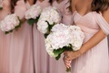bridesmaids in pink dresses carrying bouquets of white and pink flowers