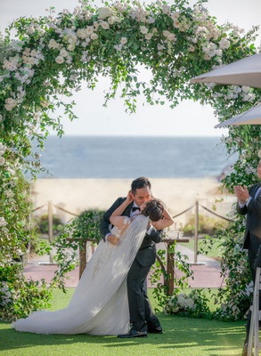 groom dips bride for a kiss during ceremony under tall floral arch