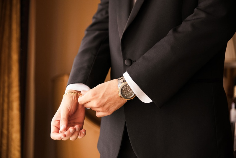 groom getting ready wearing gold bracelet and designer watch before ceremony cuffs tuxedo jacket