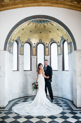 Bride showing off back of dress with groom in suit at Vibiana in gold arch marble area portrait idea