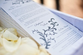 Ceremony booklets in white-lined basket with petals