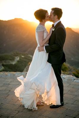 bride in reem acra wedding dress blowing in wind kisses groom in suit on helipad malibu rocky oaks