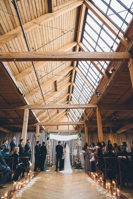 Rustic jewish wedding ceremony beams and wood floors skylight flower petals along aisle
