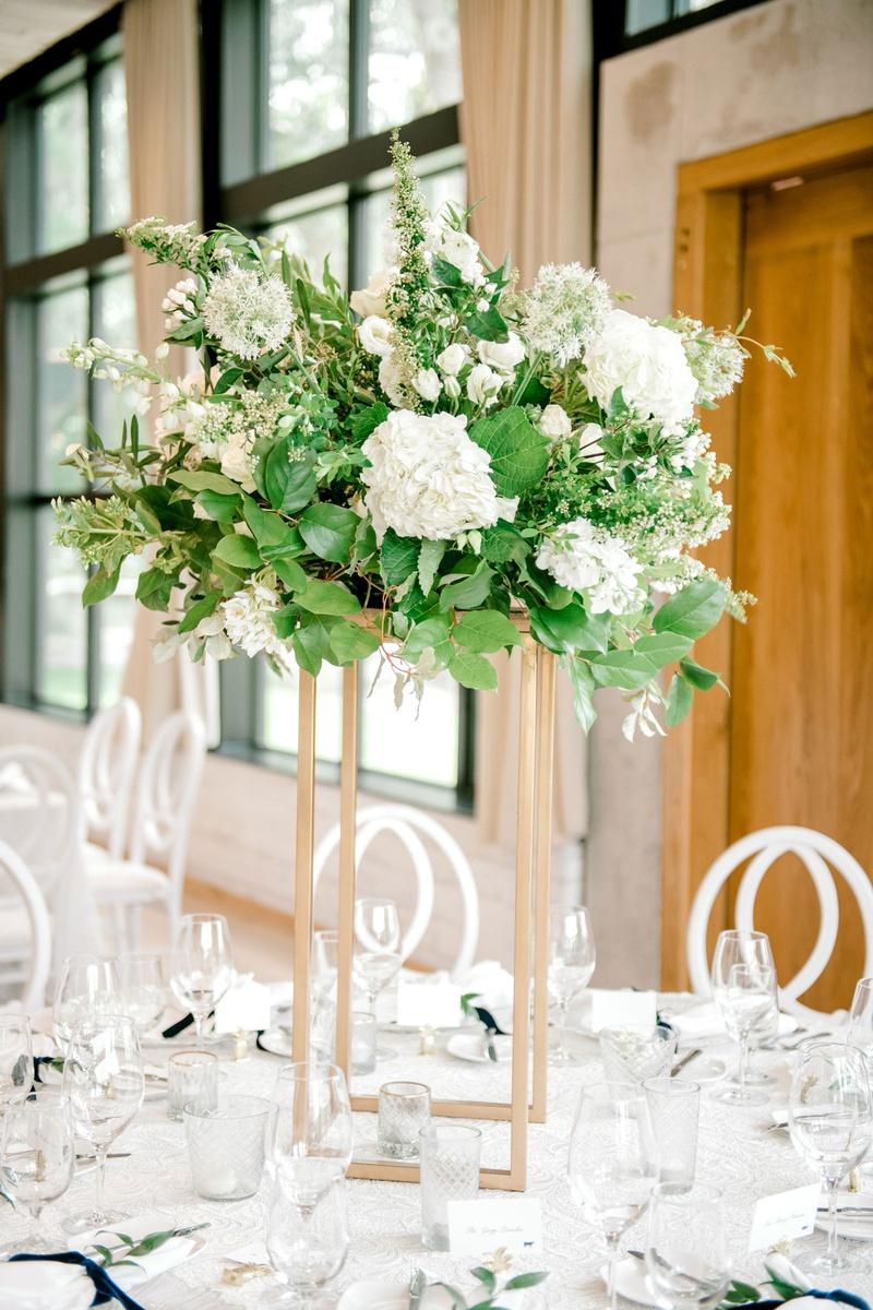 wedding reception centerpiece gold riser greenery leaves white flowers candle votives velvet ribbon