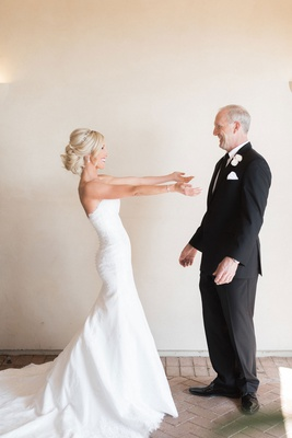 wedding idea first look with bride and father of the bride strapless wedding dress arms outreached