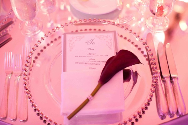 Red calla lily on wedding menu at guest seat
