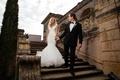 groom in tuxedo leading bride in mermaid berta wedding dress down stairs