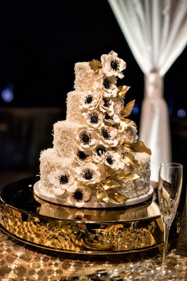 Four layer wedding cake with coconut shavings sugar anemone flowers gold leaves
