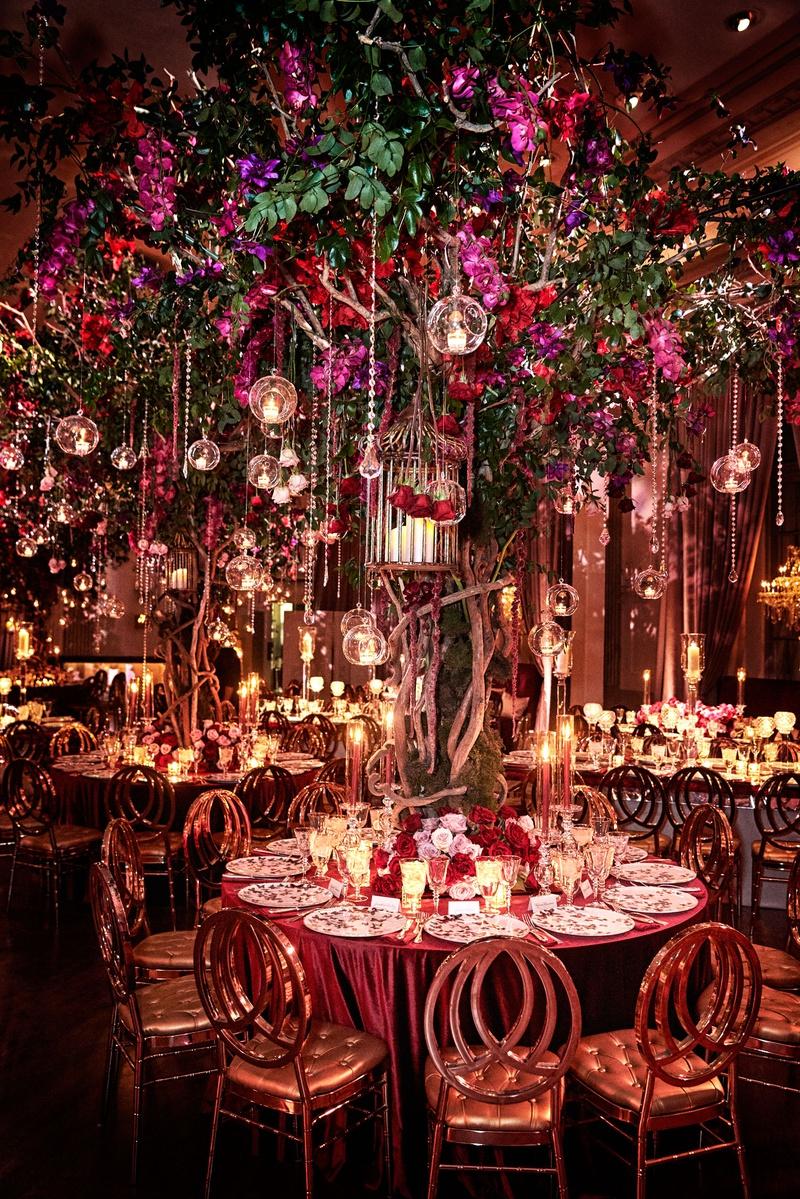 wedding reception round table large tree crystal glass orb tea light purple red flowers greenery