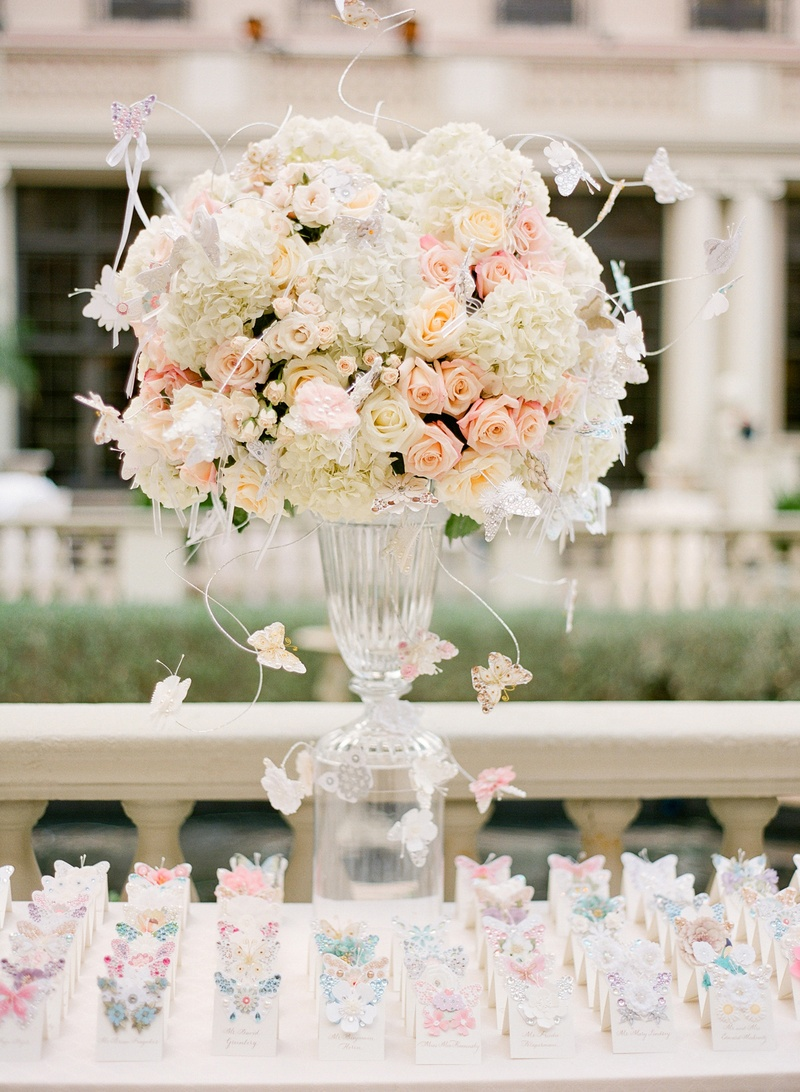 Clear vase topped with romantic flowers and butterflies