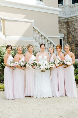 wedding party bride in romona keveza lace ball gown with bridesmaids blush pink dresses nosegay updo