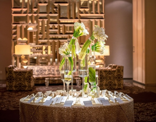 escort card table with vases filled with bunches of calla lilies
