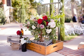 arrangement of red, white, and lavender roses displayed with wine box