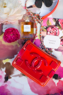 small red coco chanel purse on pink floral table linen and other chanel products chanel no 5 perfume