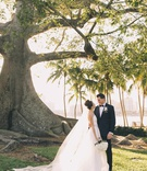 bride in romona keveza, cathedral veil, large sock bun, palm beach wedding groom in tuxedo