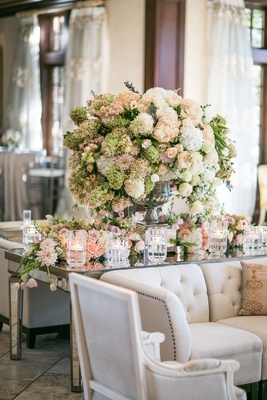 Flowers white and blush flowers on mirror table with candles and lounge furniture tufted sofa