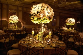 Candlelight ambient wedding reception ballroom tall rounded centerpiece designs of roses with candle
