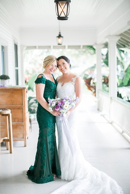 bride in lace illusion wedding dress with mother in dark green off shoulder evening gown