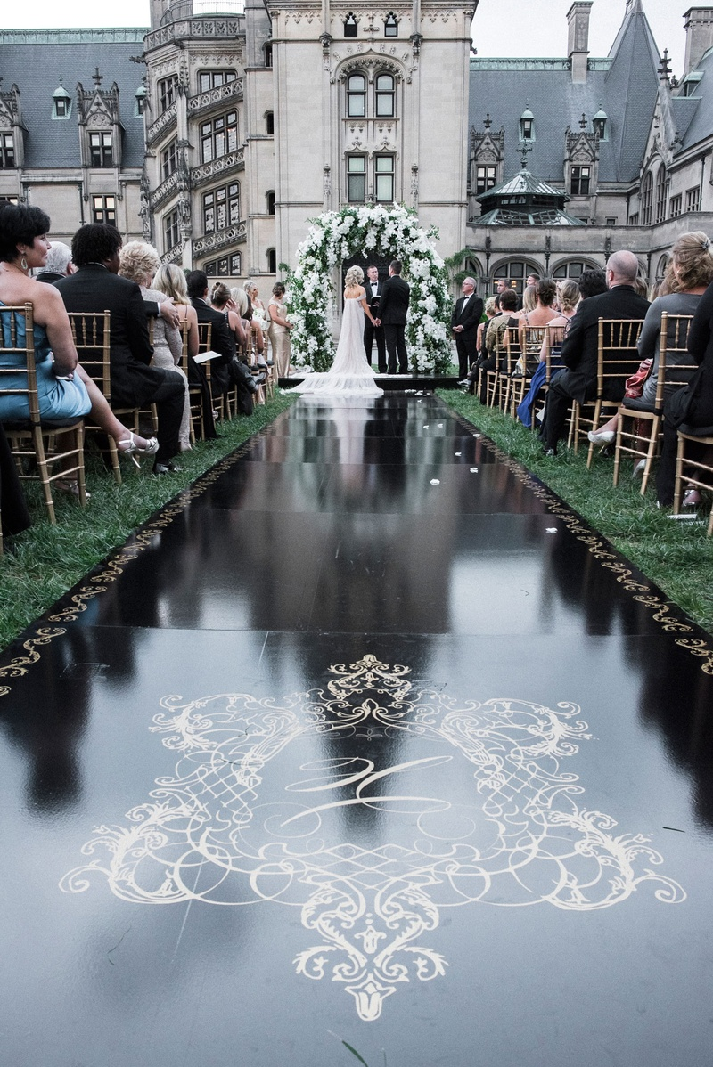 Wedding ceremony aisle black runner with gold monogram crest and border grass lawn asheville nc