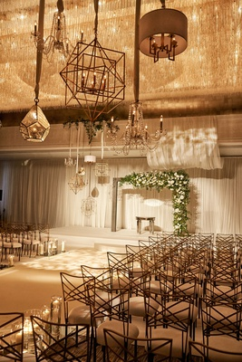 wedding ceremony indoor ballroom white drapery chandeliers asymmetrical arch wide aisle candles