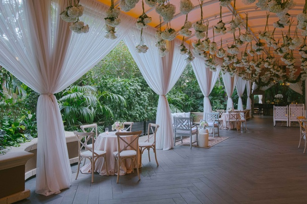 Pink drapery at outdoor cocktail hour with hydrangea bundles hanging from ceiling