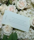 Wedding invitation on bed of hydrangeas and roses