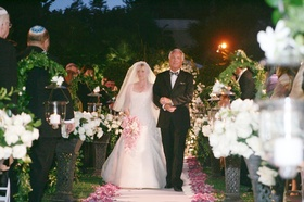Bride wearing an A-line gown and veil is escorted by her father down the aisle