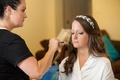Bride wearing hairpiece having makeup applied