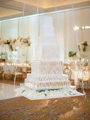 White wedding cake gold brushstroke details square tiers on white chain link swing reception space
