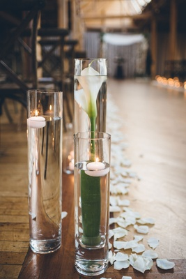Tall vase filled with calla lily and floating candles submerged wood floor rustic ceremony ideas