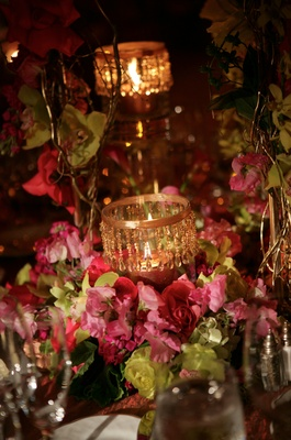 Short centerpiece with pink and green flowers and gold candles