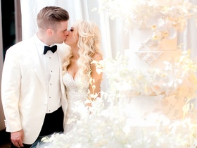 Bride and groom kiss before cake cutting at wedding reception groom outfit change