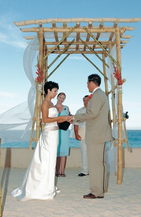 Bamboo beach wedding altar with red flowers