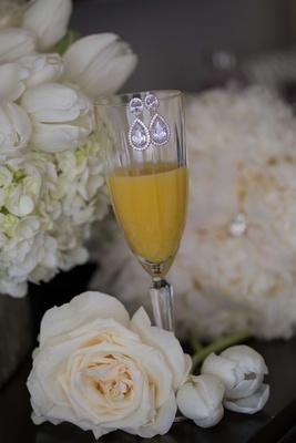 Diamond teardrop earrings on crystal champagne flute mimosa orange juice glass