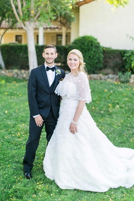 Bride in Oscar de la Renta wedding dress with cape and groom in tuxedo and bow tie