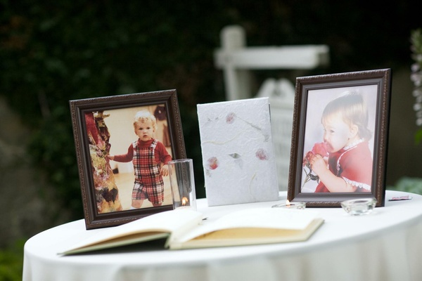 Wedding guest book table with baby photos of the bride and groom