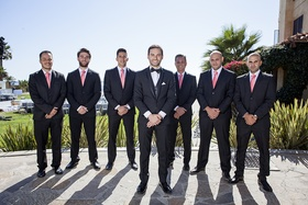 Groom in tuxedo with bow tie and groomsmen in suits and coral pink ties at destination wedding