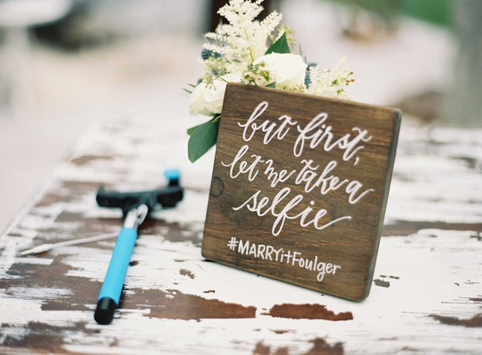 Shabby chic wedding wood sign with calligraphy wedding hashtag and selfie stick on cocktail table