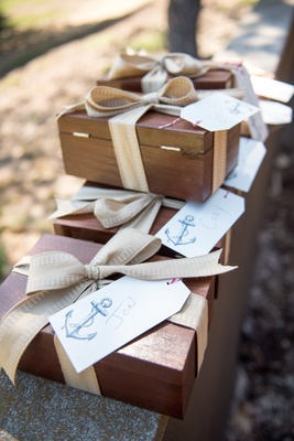 Seaside wedding with wood boxes, tan ribbons, name tags with anchor print for groomsmen