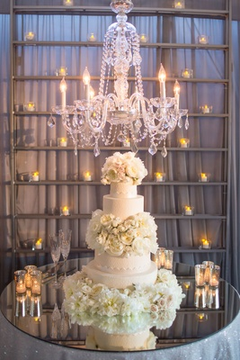 extravagant wedding cake with garden roses and peonies displayed on mirrored table under chandelier