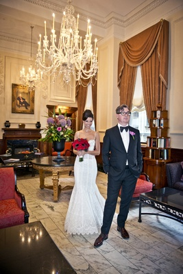 bride in pnina tornai lace wedding dress approaches groom with glasses for first look