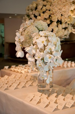 Seating card table topped with white floral arrangements