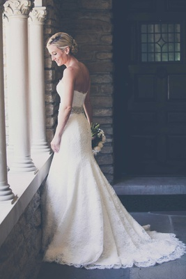 a beautiful bride smiles and stares down at ledge in her Monique Lhuillier wedding gown