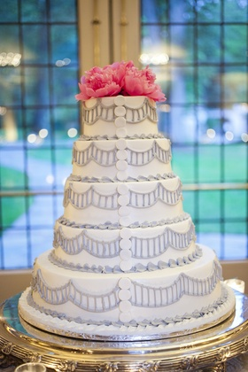 White wedding cake with design in light purple piping, buttons, hot pink peonies