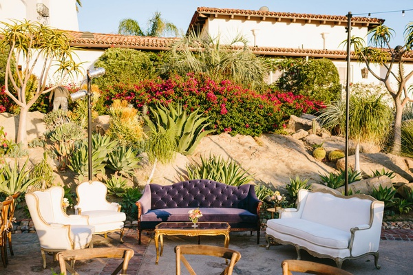 outdoor wedding reception lounge vintage furniture with desert landscaping backdrop spanish style